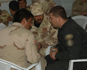 Al Anbar Iraqi Special Operations Forces Soldiers discuss a scenario during the first academics session on their first day of training March 29 at an ISOF training compound in Al Asad, Iraq. The academics course focused on face-to-face engagements and media relations concepts. The course is a portion of the overall training USSOF plans to share with ISOF as they become self sufficient in securing and maintaining the safety of the Iraqi people. It also establishes public affairs programs to help keep communities informed of their actions and intentions. (Photo illustration by Air Force Tech. Sgt. Shanda L. De Anda)
