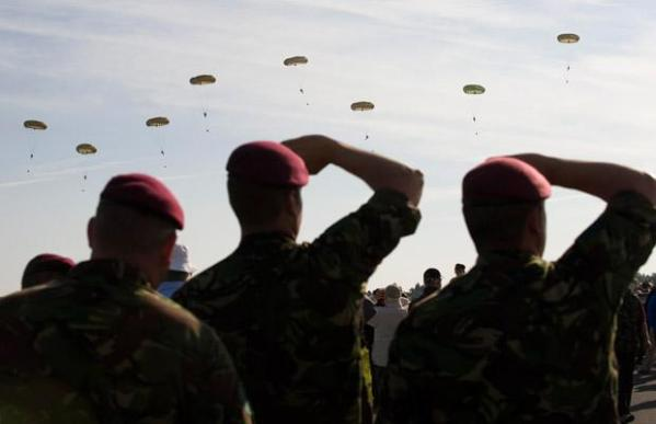 Veterans and members of the Parachute Regiment watch the memorial parachute jump near Ranville