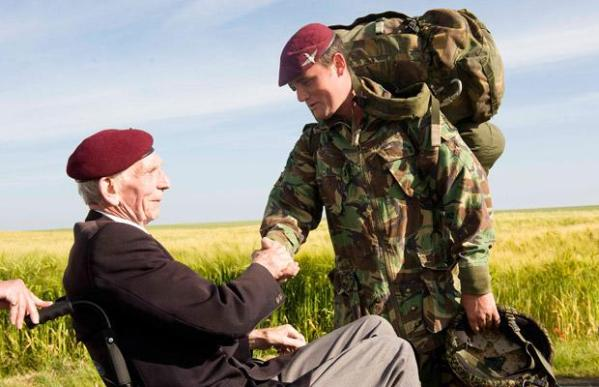 Private Douglas Baines, a veterans of the Parachute Regiment who jumped on 6th June 1944 and who liberated Ranville, greets a member of the Parachute Regiment who took part in the memorial jump
