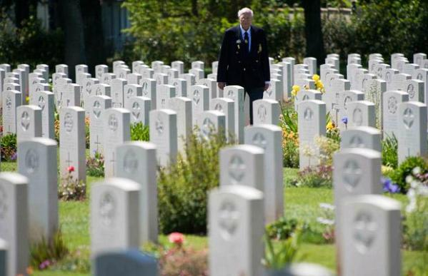 RN Veteran Ron Harris, who served on HMS Offa, visits the Ranville Cemetery