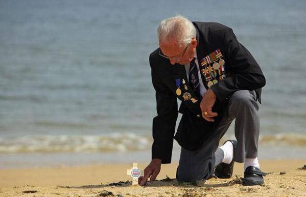 Normandy Veteran Eric Buckley, 85, from Leicester places a wooden remembrance plaque on what was the British Sword beach