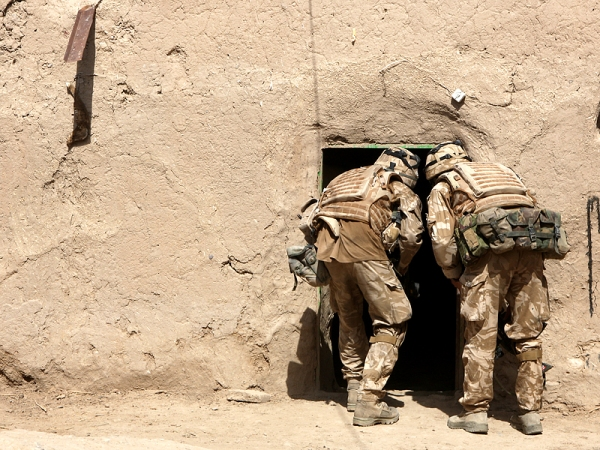 Soldiers enter a room in a compound searching for narcotics and illegal weapons.