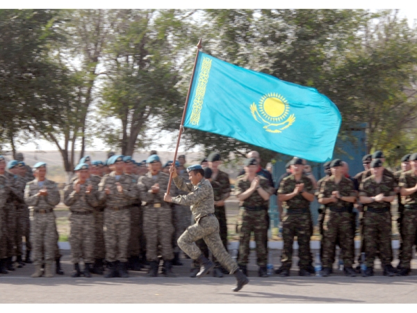 A Kazakh soldier 'runs' the Republic of Kazakhstan along the length of British and Kazakh troops at the opening ceremony of the sports day during exercise Steppe Eagle'. The exercise was a joint Kazakh British training exercise involving 160 Territorial soldiers from 7 Rifles.  PHOTO BY CHRIS FLETCHER